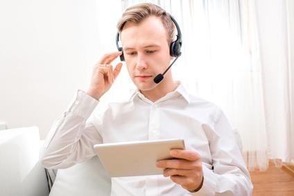 Geschäftsideen ohne Eigenkapital: service-basiertes Lifestyle Business. Mann auf Couch mach Video Konferenz über Tablet.